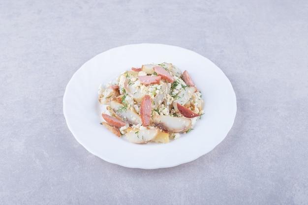 Salatteller mit würstchen auf steinhintergrund.