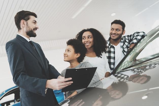Sallesman zeigt einer familie ein auto