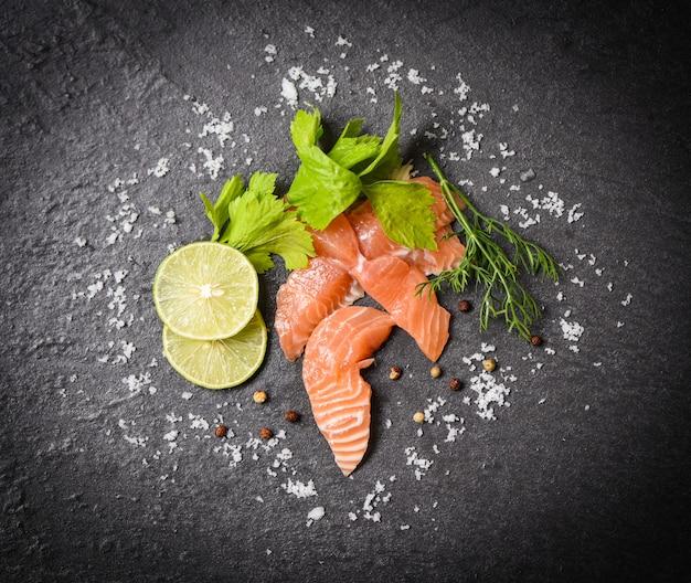 Salmon salad fish-lachsfilet auf draufsicht des schwarzblechhintergrundes von rohen lachssashimi-meeresfrüchten mit zitronenkräutern und -gewürzen