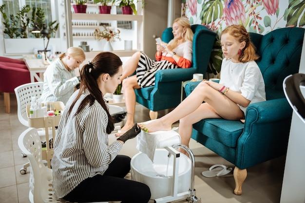 Salon mit mutter. nettes stilvolles junges mädchen, das schönheitssalon mit ihrer mutter besucht und pediküre macht