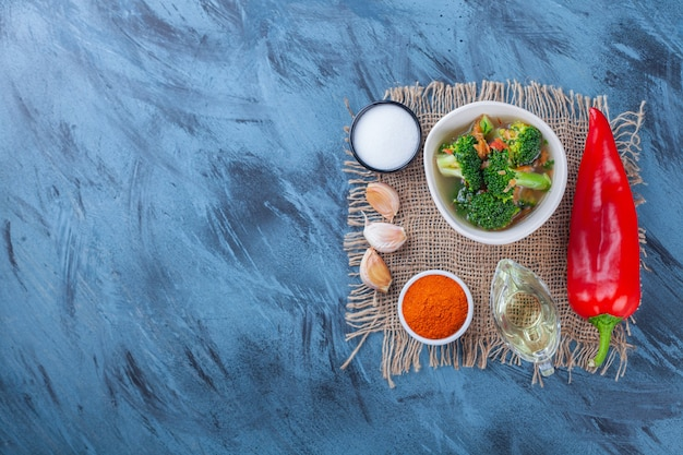 Salz, gewürze, öl, gemüse und hühnersuppe auf einer sackleinen auf der blauen oberfläche