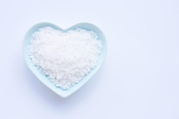 Salz in der keramischen schüssel der herzform auf weiß