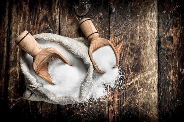 Salz in einem holzlöffel. auf hölzernem hintergrund.