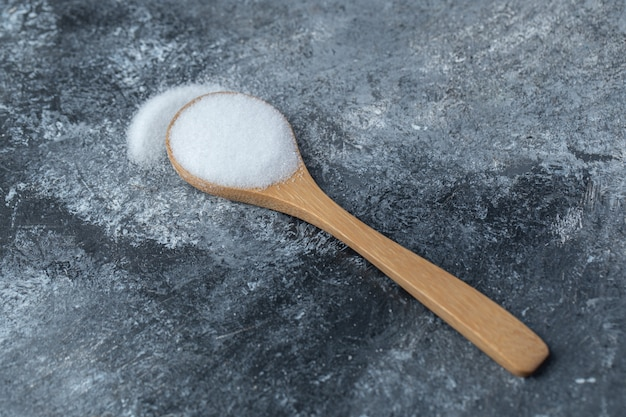 Salz in einem holzlöffel auf marmorhintergrund.