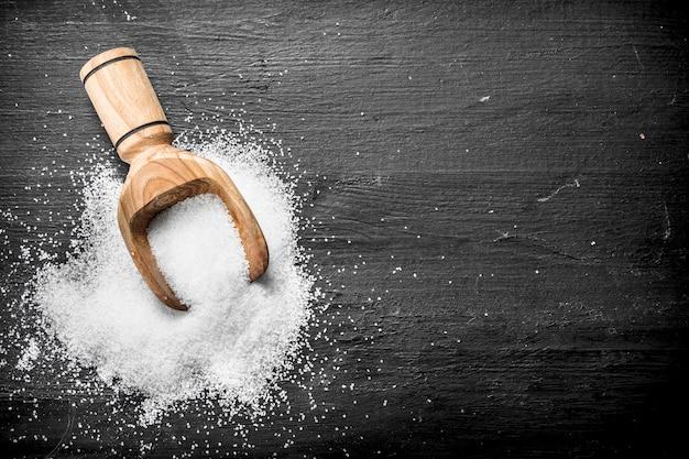 Salz in einer holzschaufel auf schwarzer tafel.