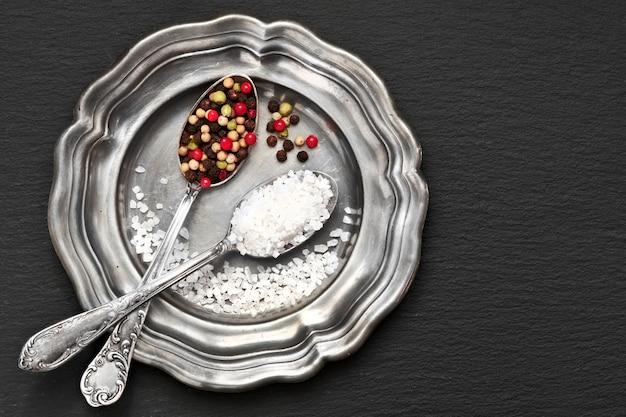 Salz in mischpfeffer in den weinleselöffeln auf alter metallplatte mit leinenserviette auf dunkelgrauem