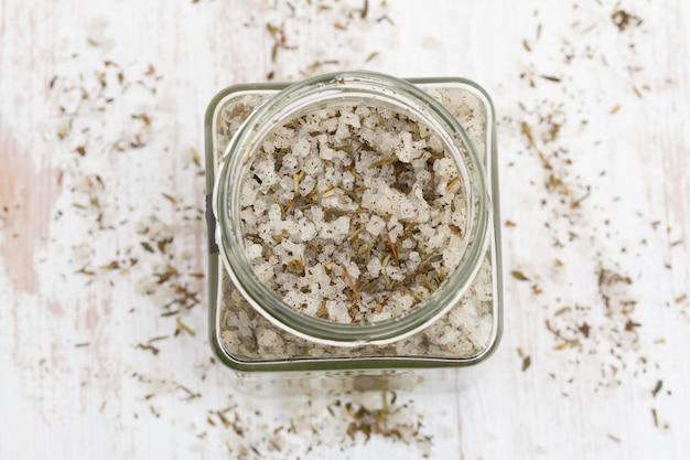 Salz mit kräutern im glas auf holzoberfläche