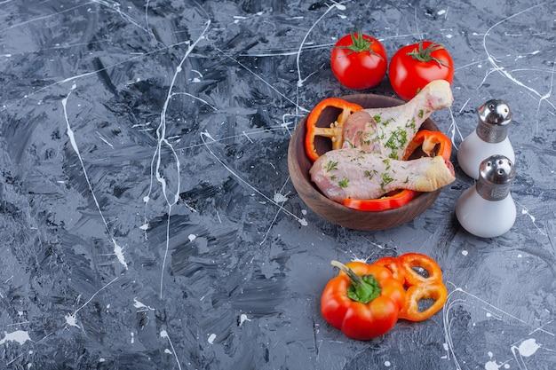 Salz, tomaten neben trommelstöcken und geschnittenem pfeffer in einer schüssel auf dem blauen hintergrund.