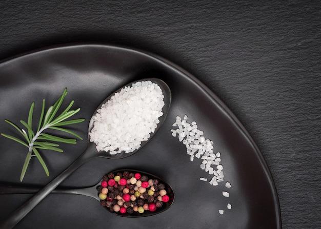 Salz und gemischter pfeffer in dunklen löffeln auf schwarzem teller auf dunklem schieferstein