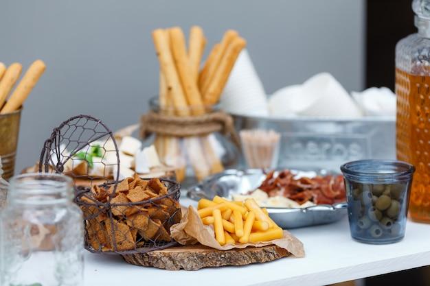 Salz- und käsebar mit verschiedenen käsesorten, trauben, oliven, jamon, honig, nüssen und snacks, dekoriert auf einem vintage-holztisch. hochzeit oder andere weihnachtsfeier im freien, picknick
