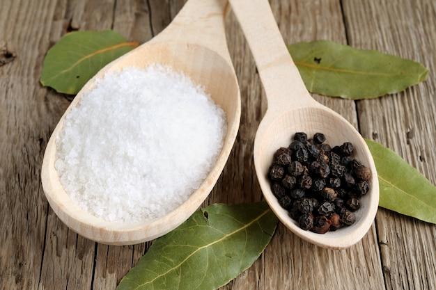 Salz und pfeffer im löffel auf holz