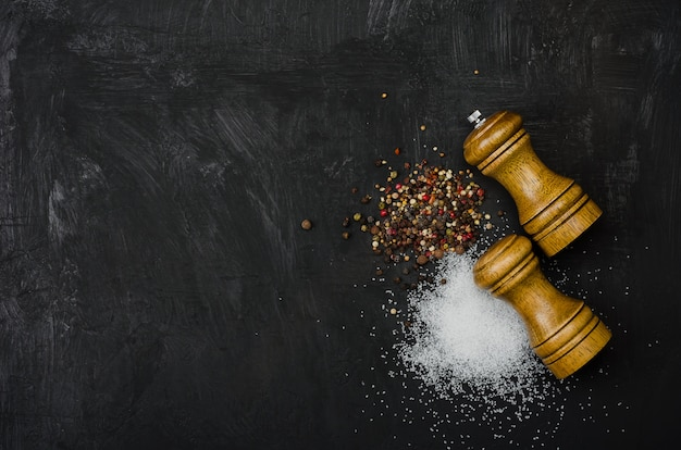Salz- und pfefferstreuer aus holz. gewürzsalz und pfeffer auf schwarzem kreidebrett