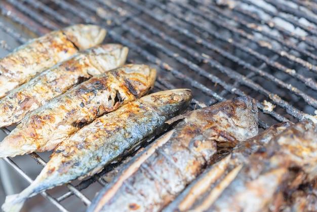 Salz-verkrusteter gegrillter seebarschfischgrill auf holzkohlenofen für verkauf am thailändischen straßenlebensmittel