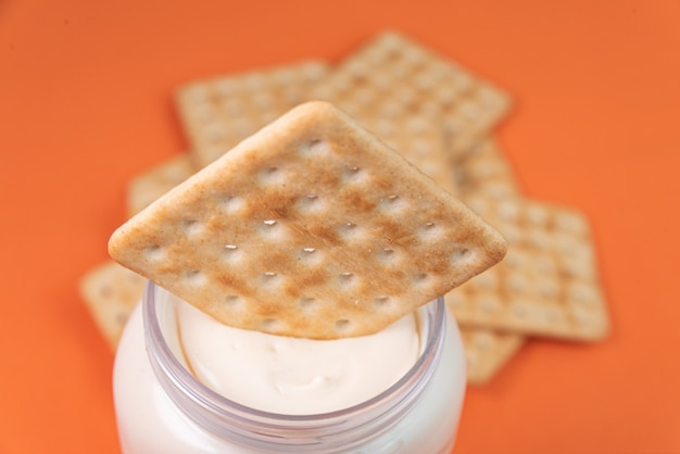 Salzcracker mit mayonnaise auf orangem hintergrund