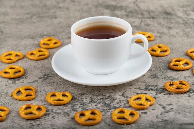 Salzige cracker-brezeln mit einer tasse schwarzen tees auf steintisch.