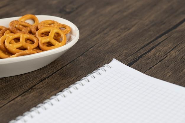 Salzige cracker-brezeln mit geöffnetem weißem notizbuch auf holztisch gelegt.
