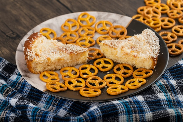 Salzige cracker-brezeln mit geschnittenem kuchen auf holztisch gelegt.