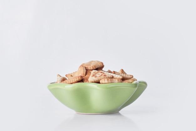 Salzige cracker in einer grünen keramikplatte auf grau