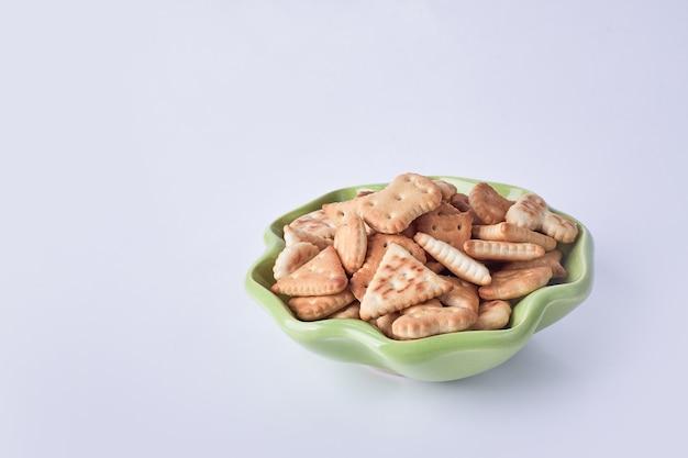 Salzige cracker in einer grünen keramikplatte.