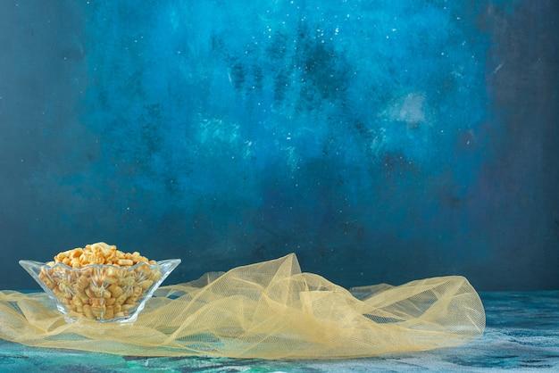 Salzige fischcracker in glasschüssel auf tüll, auf dem marmortisch.