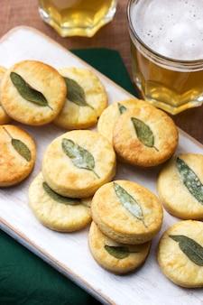 Salzige shortbread-kekse mit salbei und bier auf einem holzhocker. selektiver fokus.
