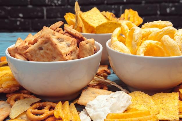 Salzige snacks. brezeln, chips, cracker auf holz. ungesunde produkte