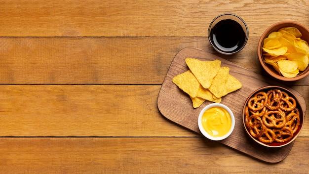 Salzige snacks der draufsicht auf hölzernem hintergrund