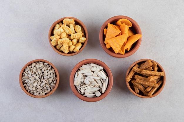 Salzige snacks in schalen auf einem beigen tisch.