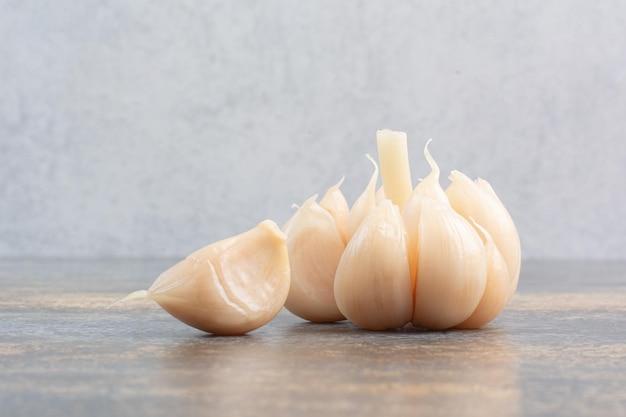 Salziger köstlicher knoblauch auf marmorhintergrund. foto in hoher qualität