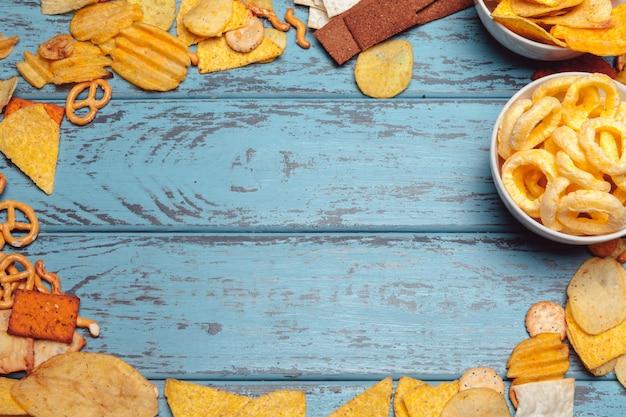 Salziger snackrahmen mit brezeln, chips, cracker auf holzoberfläche