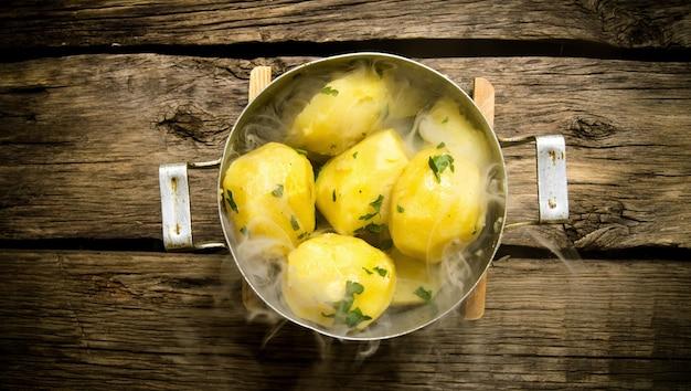 Salzkartoffeln mit kräutern und dampf auf einem holztisch