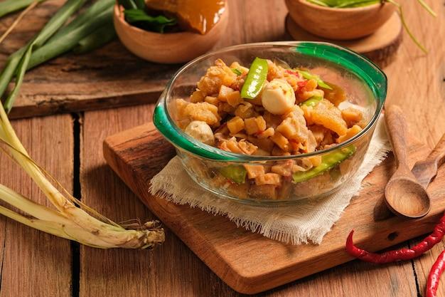 Sambal goreng kentang wird in einer schüssel auf einem holztisch serviert. ist ein traditionelles indonesisches essen, das aus bratkartoffeln mit scharfen gewürzen und erbsen hergestellt wird. spezielle gerichte, die während eid serviert werden