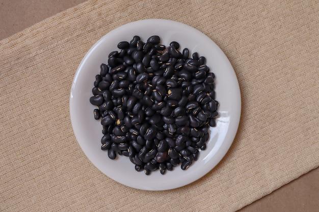 Samen der schwarzen bohnen in einer weißen keramischen schale auf einer cremefarbenen tischdecke auf einem hintergrund des braunen papiers.