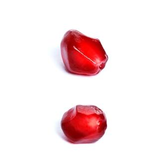 Samen einer reifen roten granatapfelnahaufnahme lokalisiert auf weißem hintergrund.
