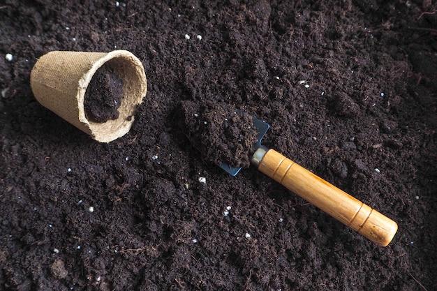 Samen im frühjahr in den boden pflanzen. hintergrund mit torftöpfen und dem boden. frühlingspflanzarbeiten.