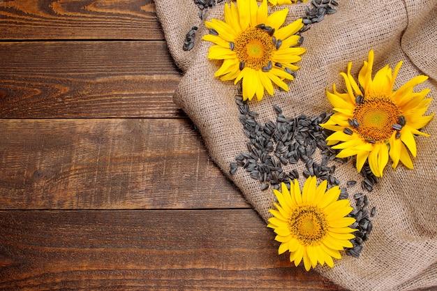 Samen mit leuchtend gelben sonnenblumen auf sackleinen auf braunem holzhintergrund. ansicht von oben mit platz für die beschriftung