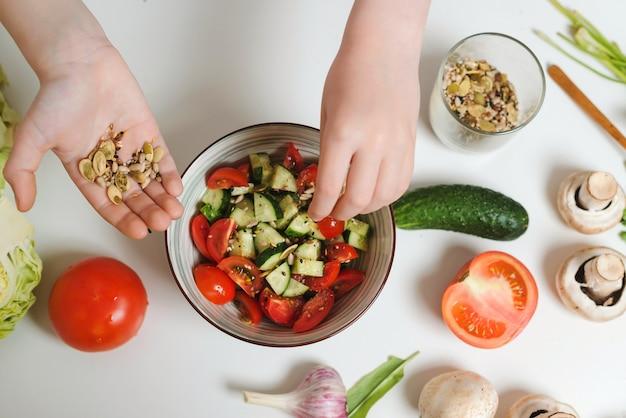 Samenmischung für salat. junger koch, der gesunden gemüsesalat in der küche kocht, draufsicht. sohn bereitet gesundes essen für das familienessen zu. konzept für gesunde ernährung und ernährung.