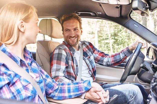 Sammeln sie momente, nicht dinge, die junges paar im auto an den händen halten und sich jedes ansehen