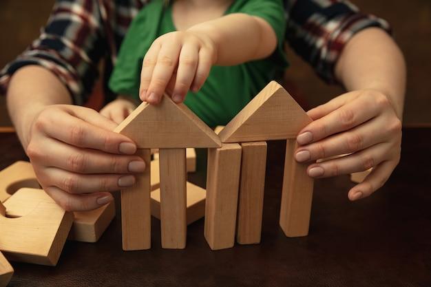 Sammeln von holzkonstrukteuren wie haus. nahaufnahme von frauen- und kinderhänden, die verschiedene dinge zusammen tun. familie, zuhause, bildung, kindheit, wohltätigkeitskonzept. mutter und sohn oder tochter.