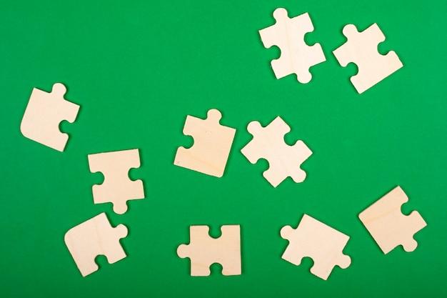 Sammle rätsel. puzzleteile auf grünem hintergrund verstreut.