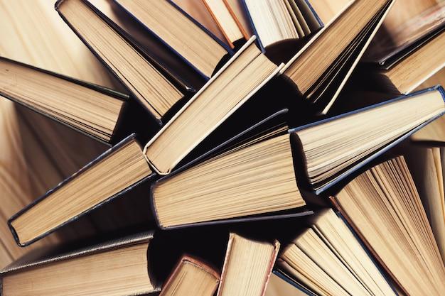 Sammlung alter bücher mit gebundenem buch in der bibliothek. vintage literatur. zurück zur schule. aufgefächerte seiten. bildungshintergrund. kopieren sie platz für text. draufsicht.