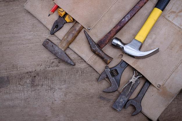 Sammlung alter handwerkzeuge für die holzbearbeitung in lederschürze auf einer rauen werkbank aus holz