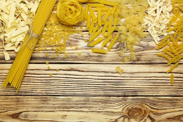 Sammlung der draufsicht der italienischen teigwaren über hölzernen hintergrund der weinlese.