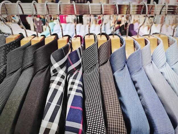 Sammlung formeller herrenhemden, die auf dem gestell hängen