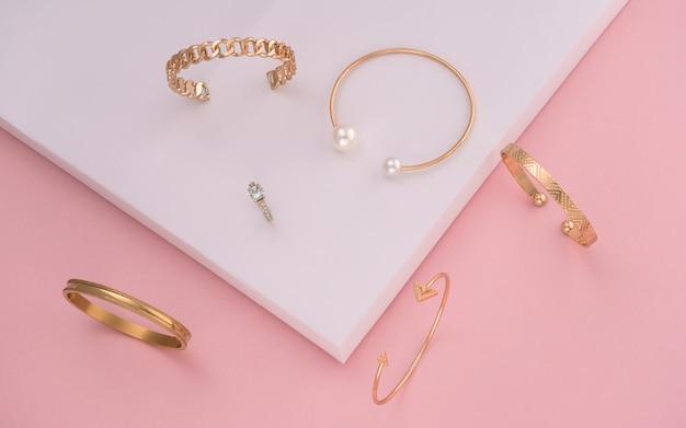 Sammlung moderner goldener armbänder auf rosa und weißem papier