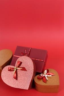 Sammlung rot und goldvalentinsgrußgeschenke auf einem roten papierhintergrund.