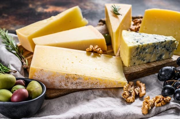 Sammlung schweizer, holländischer, französischer, italienischer käse mit nüssen und trauben. ansicht von oben