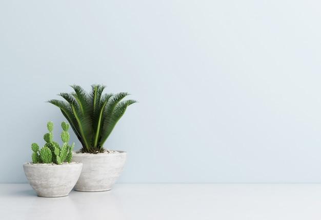 Sammlung von blumendekoration in verschiedenen töpfen topfpflanzen auf dem weißen boden vor der blauen hintergrundwand Premium Fotos