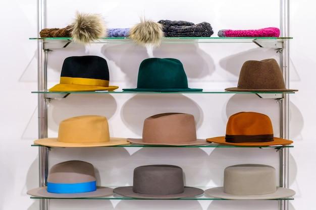 Sammlung von bunten damenhüten auf einem gestell in einer vitrine einer modeboutique auf weißem wandhintergrund.