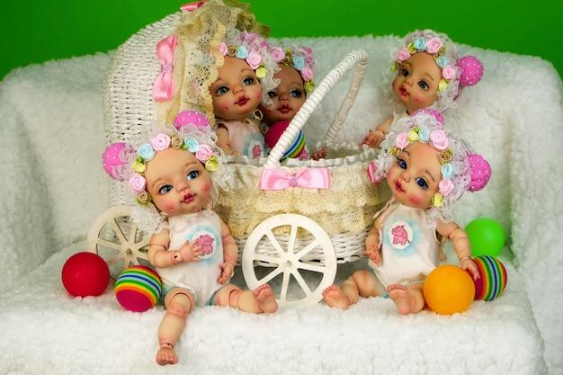 Sammlung von entzückenden handgefertigten kugelgelenkpuppen, die in dekorativem kinderwagen sitzen.